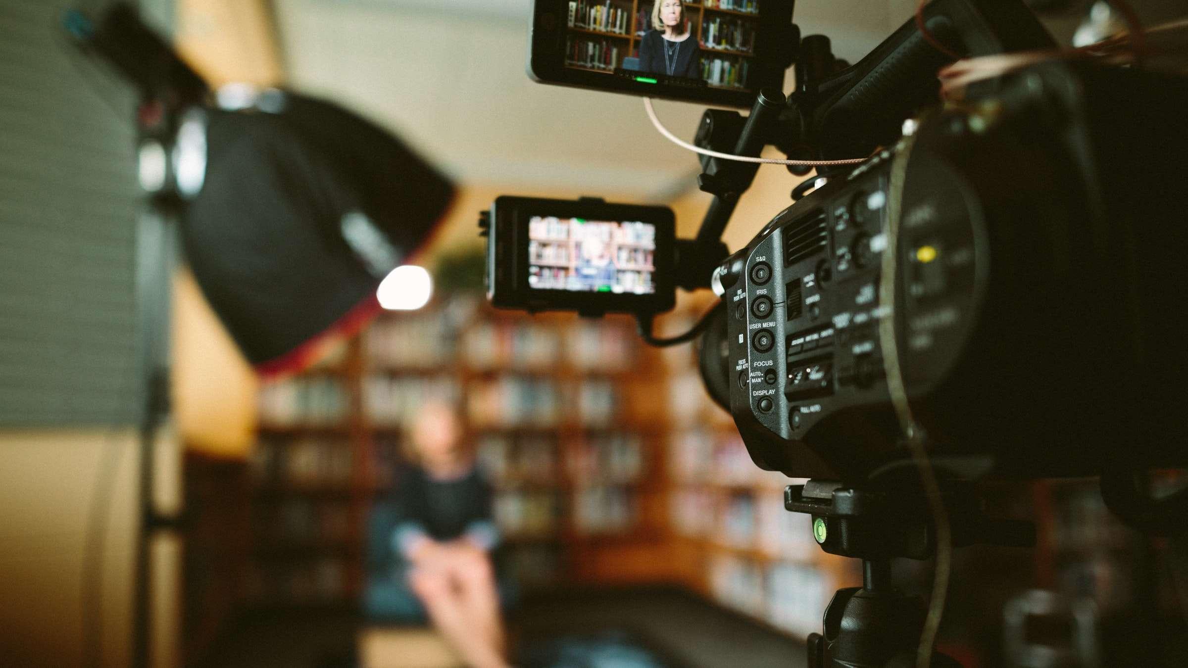 Een filmcamera filmt een persoon
